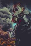 Beväpnad man med gasmasken över explosionbakgrund royaltyfri fotografi