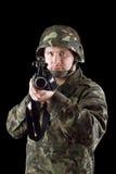 Beväpnad man som pekar ett gevär royaltyfria foton