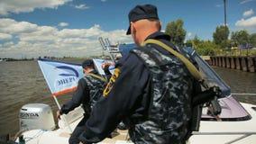 Beväpnade män stiger ombord på modern lansering med märkesflaggor stock video