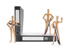 Beväpnade träskyltdockor som bevakar kontorsmappar arkivbilder