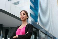 Beväpnar den unga affärskvinnan för ståenden korsat le Royaltyfri Foto