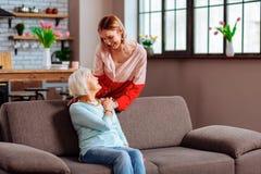 Bevallig bejaard mamma met grijs haar die veel liefs dochterpalm houden stock foto's