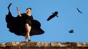 Bevallig jong meisje in een vliegende zwarte kleding en borrels tegen de blauwe hemel en de vliegende adelaars royalty-vrije stock afbeeldingen