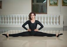 Bevallige ballerina die de spleten op de marmeren vloer doen Schitterende balletdanser die een spleet op glanzende vloer uitvoere Royalty-vrije Stock Afbeelding