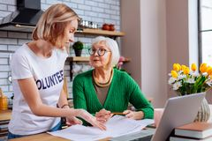 Bevallige dame die gesprek met teruggetrokken vrouw over leningsdocumenten hebben stock foto