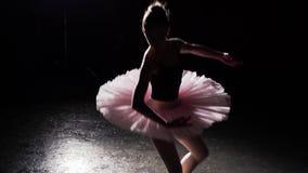 Bevallige flexibele ballerina die op haar schoenen van het pointeballet in schijnwerper op zwarte achtergrond in studio dansen He stock video