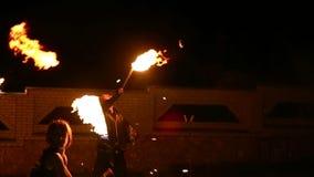 Bevallige meisjes en jongens het dansen hartstochtelijke dans met brandventilator in zijn hand De brand toont stock footage