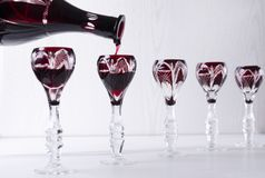 Bevanda alcolica amara rossa di versamento nei vetri d'annata Concetto della cena del buffet immagini stock libere da diritti