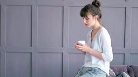 Bevanda bevente della giovane donna creativa casuale che tiene tazza che si siede sul bracciolo del sofà archivi video