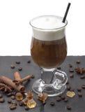 Bevanda calda in vetro con la schiuma del latte - latte del caffè, cappuccino, moccachino con il tubo, sulla tavola nera Vicino a Fotografie Stock
