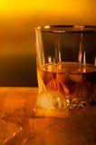Bevanda con un cubetto di ghiaccio in ambientale dorato. Immagine Stock