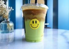 Bevanda del caffè con un fronte smily su - Latte del caffè di ghiaccio del pistacchio fotografia stock libera da diritti