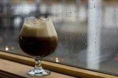 Bevanda del caffè contro la finestra piovosa fotografia stock libera da diritti