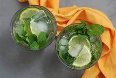 Bevanda dell'alcool di Mohito Due vetri con le bevande del cocktail ed i cubetti di ghiaccio e gli agrumi delle calce Immagini Stock