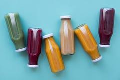 Bevanda della disintossicazione in bottiglie su fondo blu Stile naturale dell'alimento biologico fotografie stock