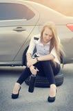 Bevanda della ragazza un alcool Automobile rotta su un fondo La donna si siede su una ruota riparazione della donna un'automobile Fotografie Stock