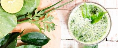 Bevanda di erbe verde della disintossicazione con gli ingredienti sul tagliere Fotografia Stock