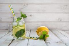 Bevanda di estate, acqua con il limone, ghiaccio e menta in barattolo di muratore su un fondo di legno bianco Fotografie Stock Libere da Diritti