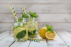 Bevanda di estate con il limone, il ghiaccio e la menta in barattolo di muratore su un fondo di legno bianco Fotografia Stock Libera da Diritti