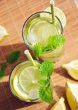 Bevanda di estate con il limone, la limetta, la menta ed il ghiaccio in vetri Fotografie Stock