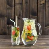 Bevanda dietetica della disintossicazione con il succo di limone, le foglie rosse della fragola, del cetriolo e di menta in chiar Immagini Stock Libere da Diritti