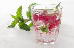 Bevanda fredda di estate con i lamponi, il ghiaccio e la menta fresca Immagine Stock