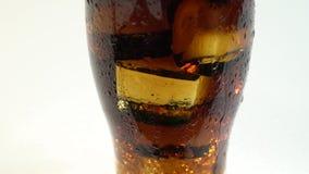 Bevanda gassosa in un vetro dei sibili e delle bolle del ghiaccio Priorità bassa bianca Fine in su stock footage