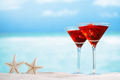 Bevanda rossa sulla spiaggia, sull'oceano, sulla spiaggia di sabbia bianca e sulla vista sul mare Fotografie Stock