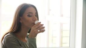 Bevanda sana Bella donna che beve yogurt naturale video d archivio