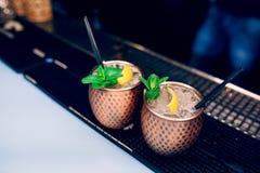 Bevanda sana esotica del cocktail del vaso dorato con la cannella di combustione e la calce, bevanda della menta su un contatore  fotografie stock libere da diritti