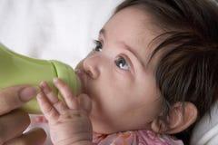 Bevande del bambino dalla bambino-bottiglia Fotografia Stock Libera da Diritti