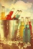 Bevande di estate in secchiello del ghiaccio alla spiaggia con lo sguardo d'annata Fotografia Stock