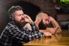 Bevande di ordine al contatore della barra Uomini con le cuffie e lo smartphone che si rilassano alla barra Eviti la comunicazion fotografie stock libere da diritti