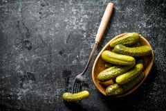 Bevarade gurkor på en platta med en gurka på en gaffel arkivbild