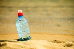 Bevarage botella de bebida del agua en una playa arenosa Imagenes de archivo