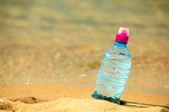 Bevarage. bottle of water drink on a sandy beach. Royalty Free Stock Images