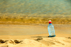 Bevarage. bottle of water drink on a sandy beach. Stock Photography