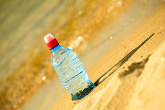 Bevarage. bottle of water drink on a sandy beach. Royalty Free Stock Photography