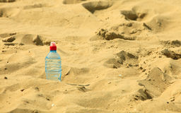 Bevarage. bottle of water drink on a sandy beach. Royalty Free Stock Photos