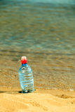 Bevarage. bottle of water drink on a sandy beach. Royalty Free Stock Photo
