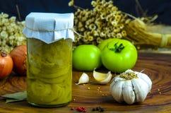 Bevarat vegetariskt matbegrepp På burk salladslök i en krus på träbakgrund arkivbild