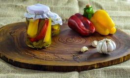 Bevarat vegetariskt matbegrepp Rött på burk, gör grön gula peppar i en krus på träbakgrund arkivbild