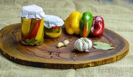 Bevarat vegetariskt matbegrepp Rött på burk, gör grön gula peppar i en krus på träbakgrund royaltyfri bild