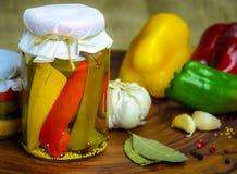 Bevarat vegetariskt matbegrepp Rött på burk, gör grön gula peppar i en krus på träbakgrund royaltyfri fotografi