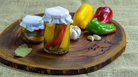 Bevarat vegetariskt matbegrepp Rött på burk, gör grön gula peppar i en krus på träbakgrund arkivbilder