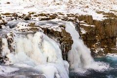 Bevattna att falla på monteringen Kirkjufell på vintern i Island Vattenfa arkivbilder