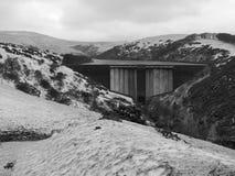 Bevattna att flöda över den Meldon fördämningen i snön, den Meldon behållaren, Dartmoor Arkivfoton