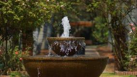 Bevattna att flöda från en stenspringbrunn i botaniska trädgården av Bogota Arkivbilder
