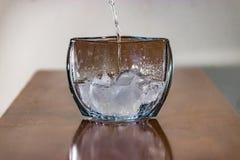 Bevattna att hälla över is in i snallkristallvasen fotografering för bildbyråer