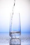 Bevattna att hälla in i en tredjedel fulla dricka exponeringsglas på droppar Arkivbilder